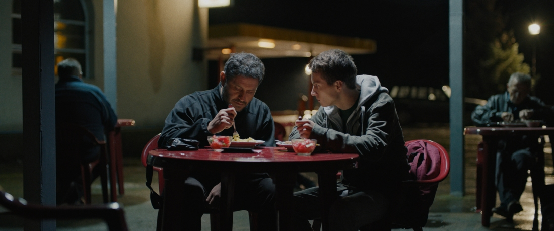 Mustafa and Alim are sat at a red plastic table eating their individual meals. Mustafa, the father, is in a coat and staring down at his food. Alim, the son, is in a black coat with a grey hoodie, staring at his dad eating.
