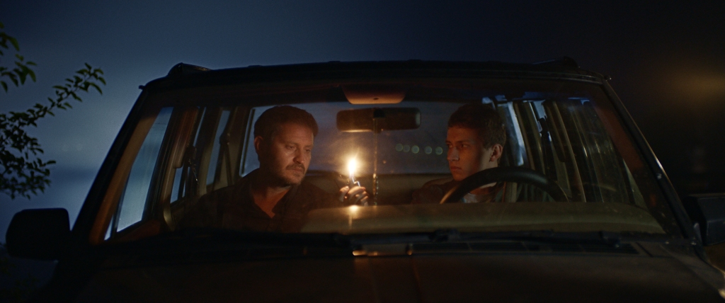 Mustafa and Alim are sat together in the car staring at Nazim's lighter which is aflame between them. It's dark and the warmth of the flame lights their faces