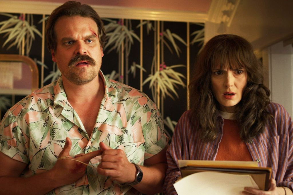 Hopper (left) and Joyce (right) stand next to one another with their jaws dropped. Hopper is wearing a green and pink pastel shirt whilst Joyce wears a dark purple shirt with a dark orange ringer top underneath.