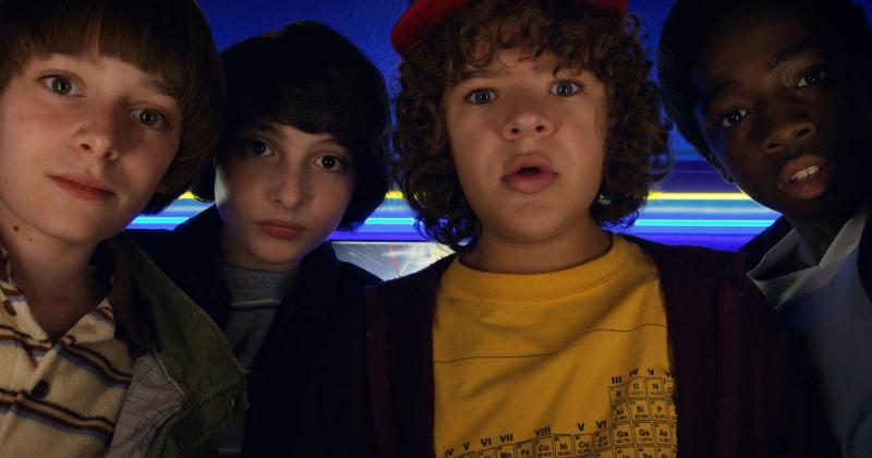 Image is from the TV Show 'Stranger Things'. Four young boys crowd in front of the screen, appearing to look directly at the camera which is below them.
