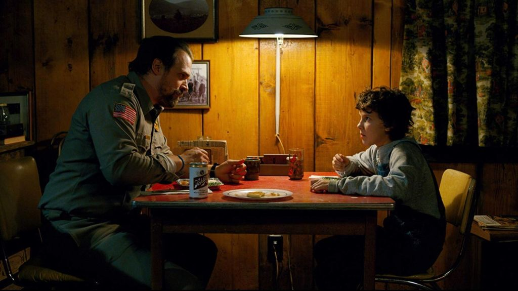 Hopper and El sit opposite one another at a small table which is only lit by a lamp that is sat directly one the table. They are eating and in mid-conversation.