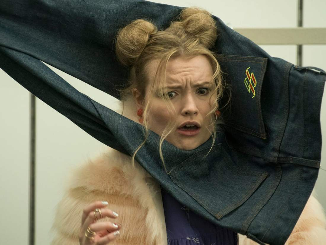 Image is from the film 'Slaxx' (2020). A young woman wearing a fur coat and space buns is being strangled by a pair of jeans.