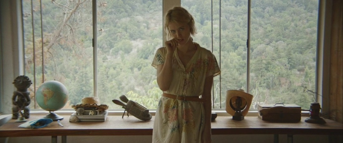 Image is from the film 'Always Shine' (2016). The film still shows Anna, now performing as Beth, in the middle of the frame. She's looking right into the camera with her head tilted to one side, almost like she knows viewers are watching her performance. She's biting on her thumb, reminiscent of an innocent child as she's trying to mimic the body language of Beth. She looks nervous and timid. Anna is wearing Beth's button-up romper suit with a flower pattern, with a light brown belt in the waist. In the background is a long desk visible – filled with miscellaneous objects including a globe and a cowboy hat all in a row – along with a big window showing the green nature of Big Sur.