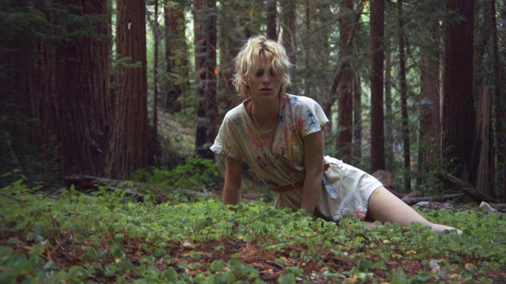 Image shows Anna – still looking like Beth in her physical appearance – waking up in the woods of Big Sur. She's alone and she looks disoriented in her facial expression, with a confused expression as she looks ahead of herself with a mixture of emptiness and fear in her eyes. She's still wearing Beth's button-up romper suit with a flower pattern with a light brown belt in the waist.