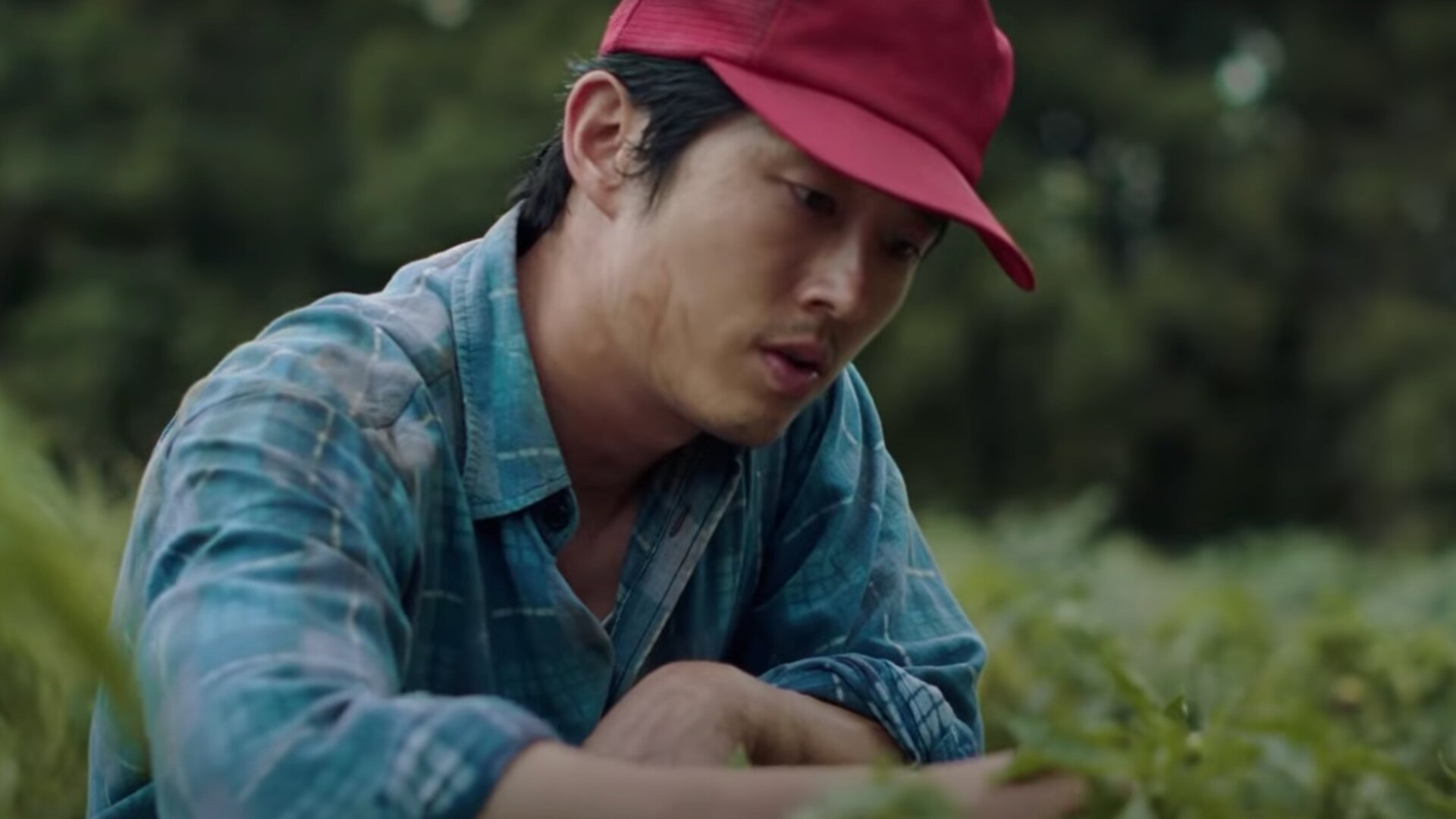 Image is from the film 'Minari' (2020). A man in his thirties looks down at the ground. He is wearing a red baseball cap and a blue plaid shirt.