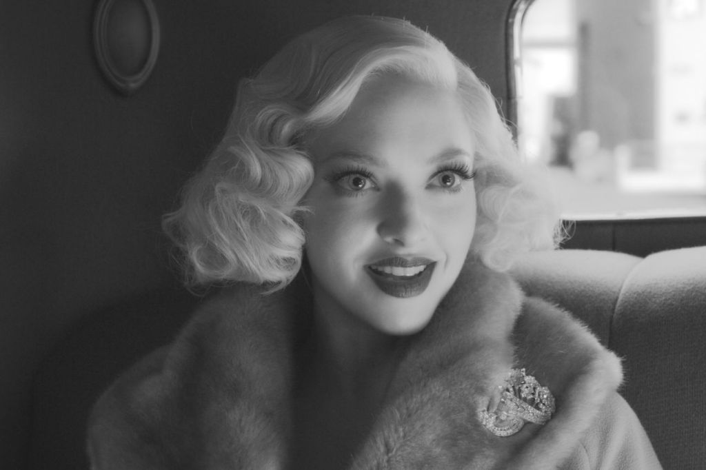 Image is from the film 'Mank' (2020). A young woman in a fur lined coat sits in the back of a car. She is wearing dark lipstick and has her hair curled in a 1920s fashion. The image is in black and white.