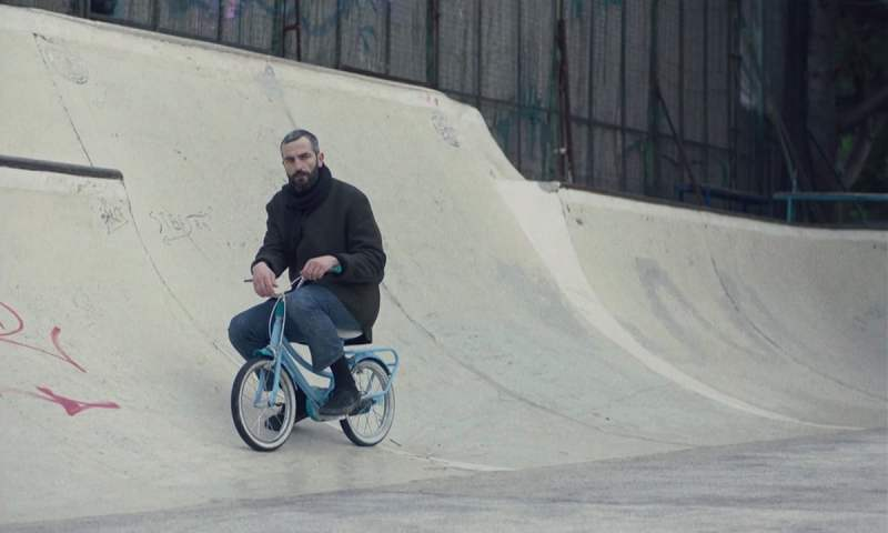 Image is from the film 'Apples' (2020). A middle aged man is posed on a bmx bike in a skate park.