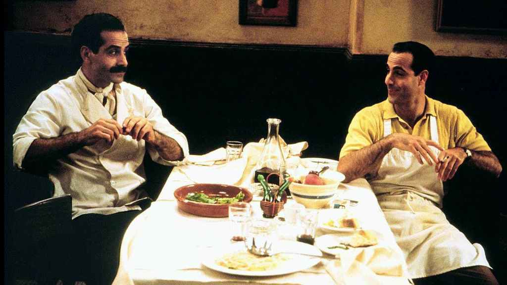 Image is from the frilm 'Big Night' (1996). Two chefs sit opposite one another with their hands to their chests and talk to one another. They sit either side of a white, clothed, table which is covered with half-eaten food.