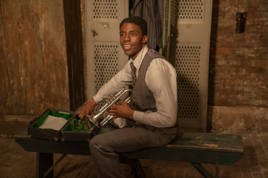 Image is from the film 'Ma Rainey's Black Bottom' (2020). A young black man wearing a striped shirt and a grey patterned suit begins to assemble a trumpet.
