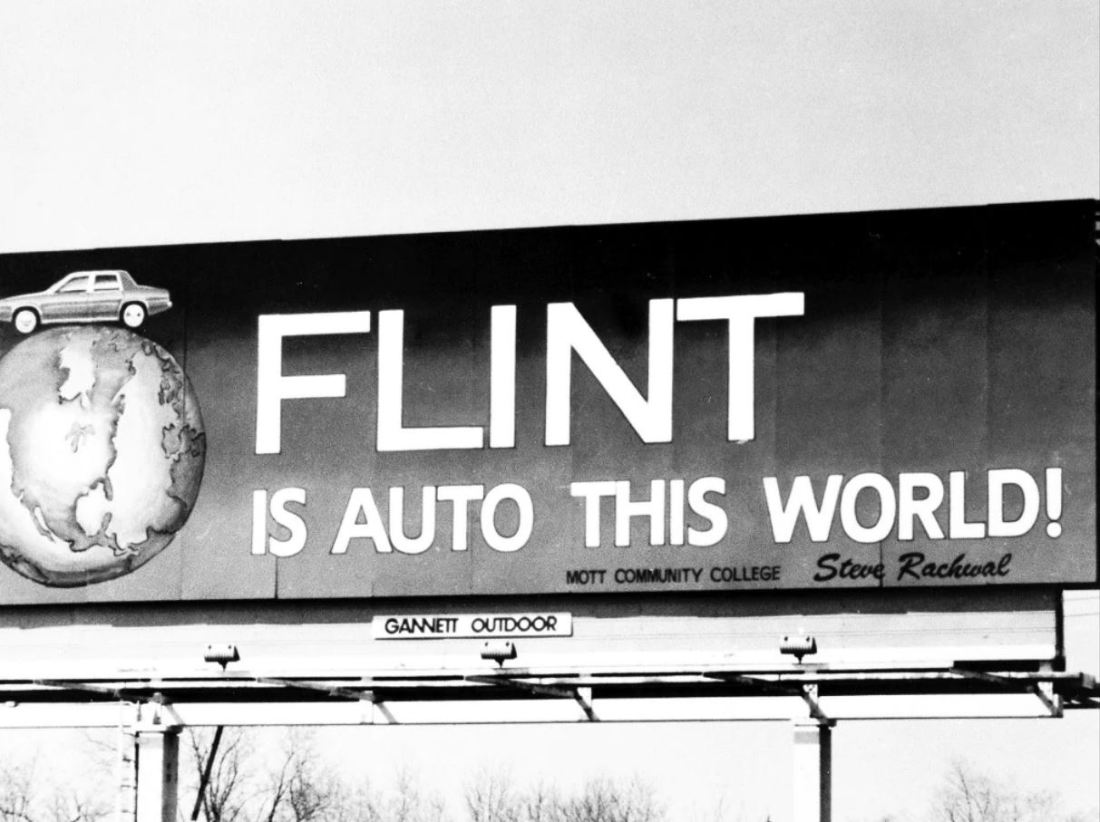 """Image is from the documentary 'Roger & Me' (1989). Image shows a billboard that has a cartoon car on top of a globe alongside the words """"FLINT IS AUTO THIS WORLD!"""""""