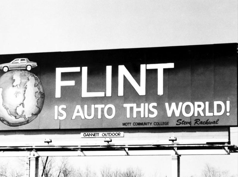 "Image is from the documentary 'Roger & Me' (1989). Image shows a billboard that has a cartoon car on top of a globe alongside the words ""FLINT IS AUTO THIS WORLD!"""