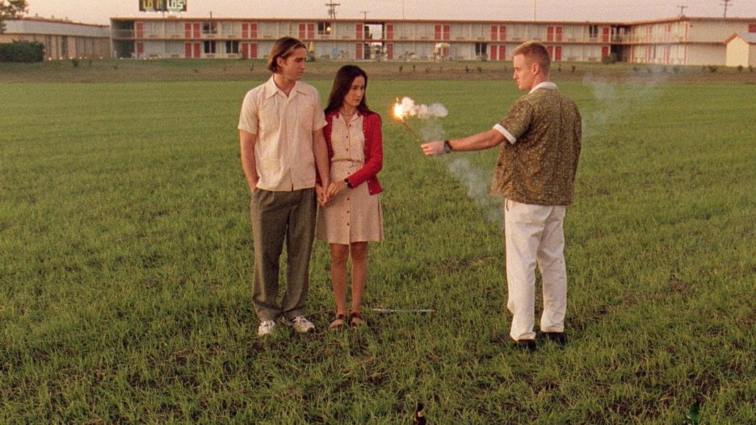 Image is from the film 'Bottle Rocket' (1996). In a field that is backed by a small block of apartments, a young man sets off a small explosive in front of a couple, who are holding hands.