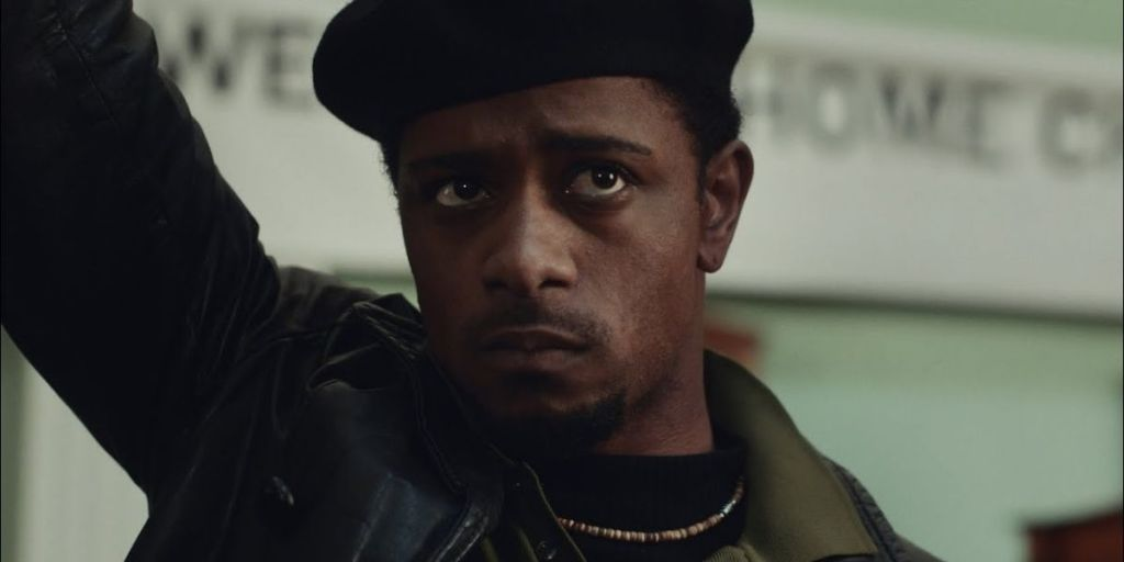 Image is from the film 'Judas and the Black Messiah' (2021). A young black man wearing a dark jacket and a black hat rests his hand above his head.