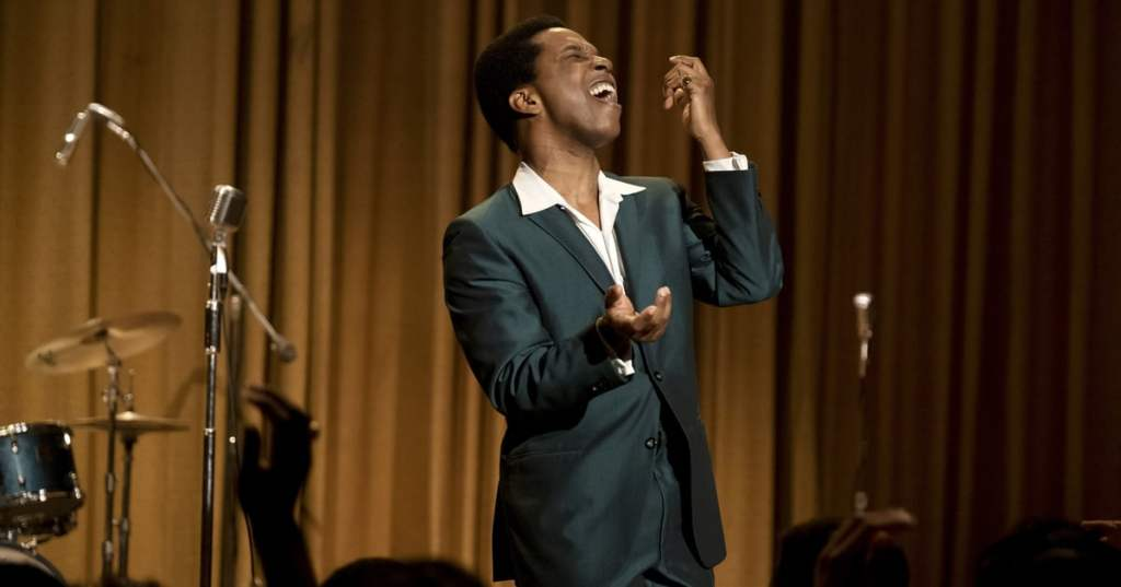 Image is from the film 'One Night in Miami' (2020). Leslie Odam Jr. portrays Sam Cooke, and is singing on stage in a black suit. In front of him an audience applauds and behind his is a brown curtain and drumkit.