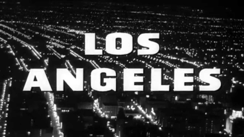Image is from the documentary 'Los Angeles Plays Itself' (2003) Image shows the lit up strips of Los Angeles by night, with the city's name overlaid in block text.
