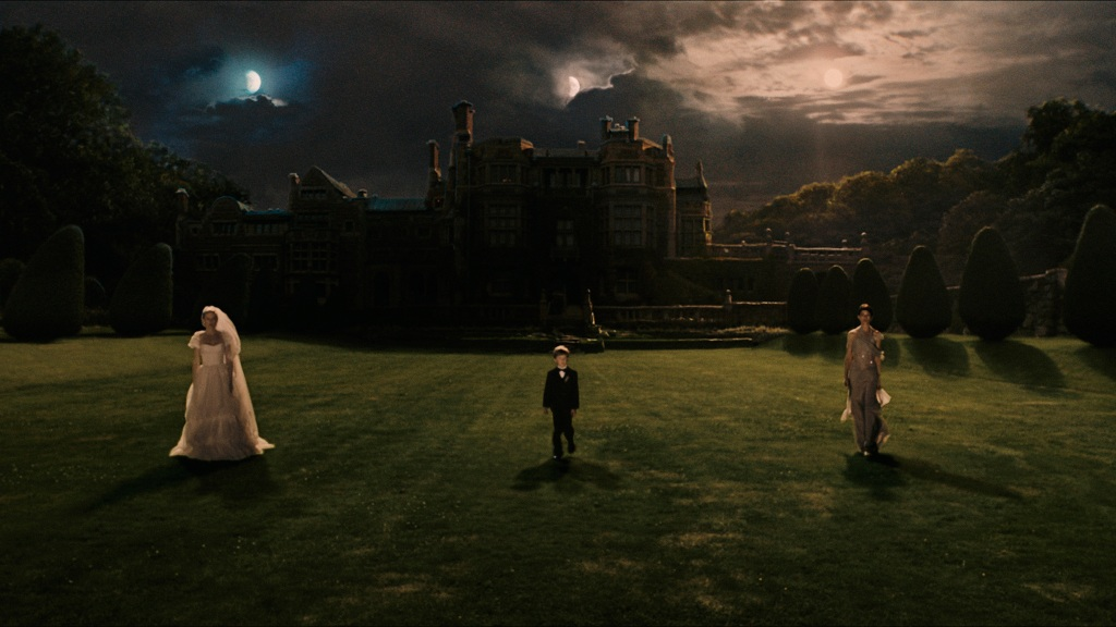 Three people stand in front of a shadowed castle that stands in front of a cloudy night sky that shows three moons. On the left is a woman wearing a wedding dress. In the middle is a child wearing a suit. On the right is a woman wearing a purple dress.