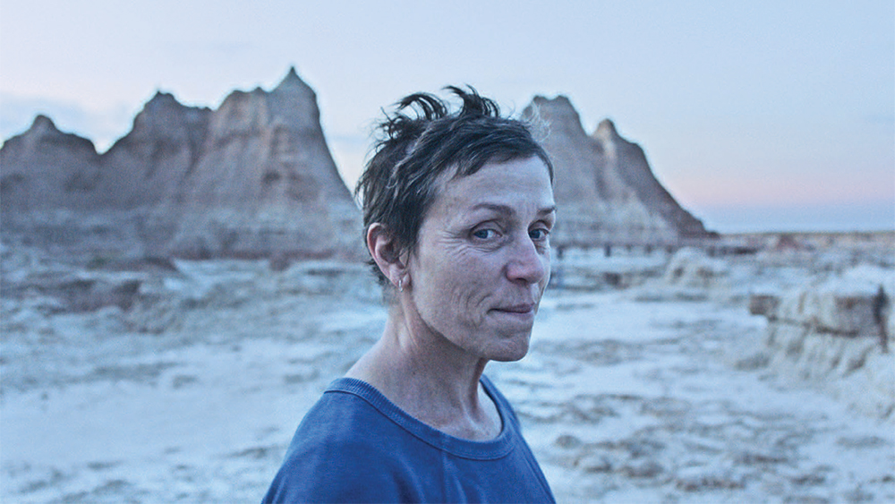 Image from the film 'Nomadland' (2020). A woman with short hair wearing a blue t-shirt stands in front of a snow covered, mountainous landscape.