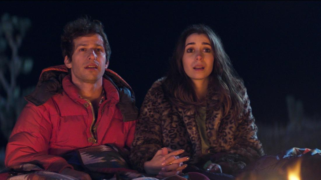 Image is from the film 'Palm Spring' (2020). A man in a red coat holds the hand on a woman wearing a leopard print fur coat. They are sat in front of a fire at night, covered in blankets. They both are looking at something in the distance.