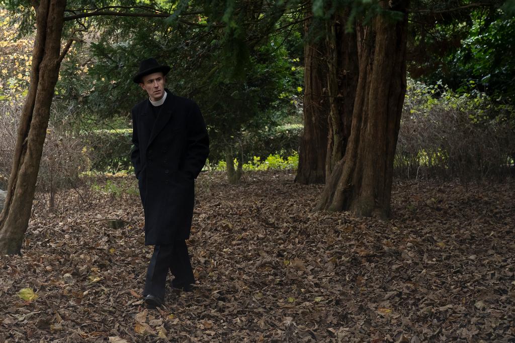 The vicar Linus (John Heffernan) looks pensive as he walks amongst fallen leaves