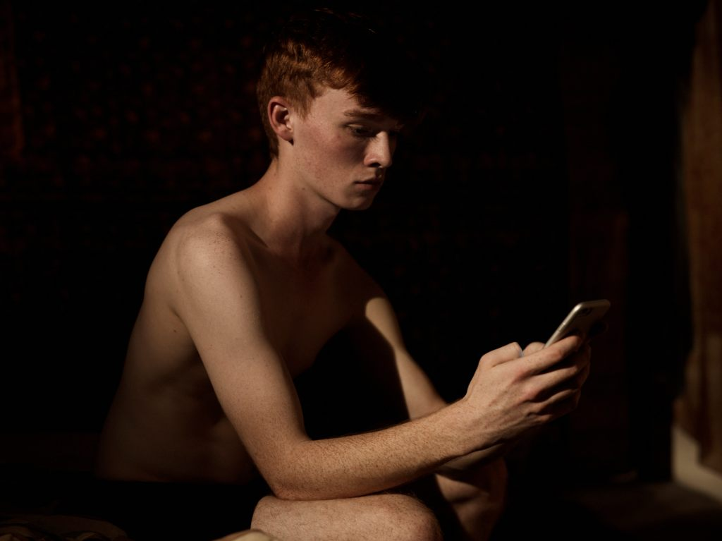 Sequin is sat in darkness, he is only wearing a pair of shorts and his pale skin is illuminated by white light. his attention is focused on the phone in his hand