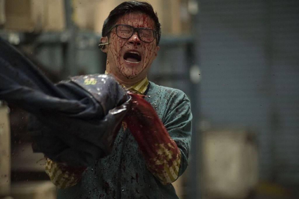 Screen grab from the film Slaxx (2020)- One of the male characters is holding a pair of jeans with blood all over him.