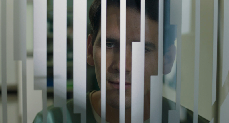 A row of window blinds obscure most of a young man's face, who is looking through the blinds and the window with an intense gaze.