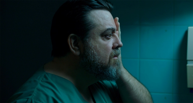 Image is from the film 'The Dose' (2021). A man in green scrubs holds his hand over his eye as he looks into a bathroom mirror.