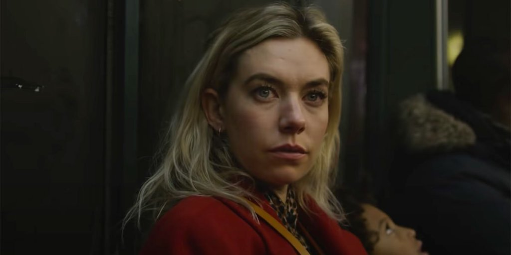 Image is from the film 'Pieces of a Woman' (2020). A blonde woman wearing a red coat sits in a subway carriage. She is looking at something in front of her.