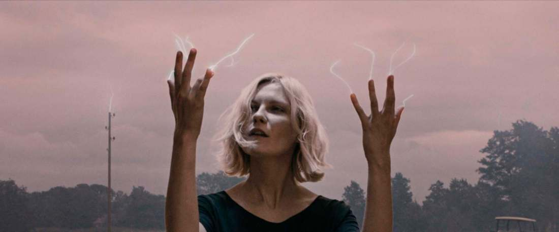Image is from the film 'Melancholia' (2011). In front of a pink, cloudy sky that is lined with trees, a young woman holds her hands up. Lightning is erupting from her fingertips.