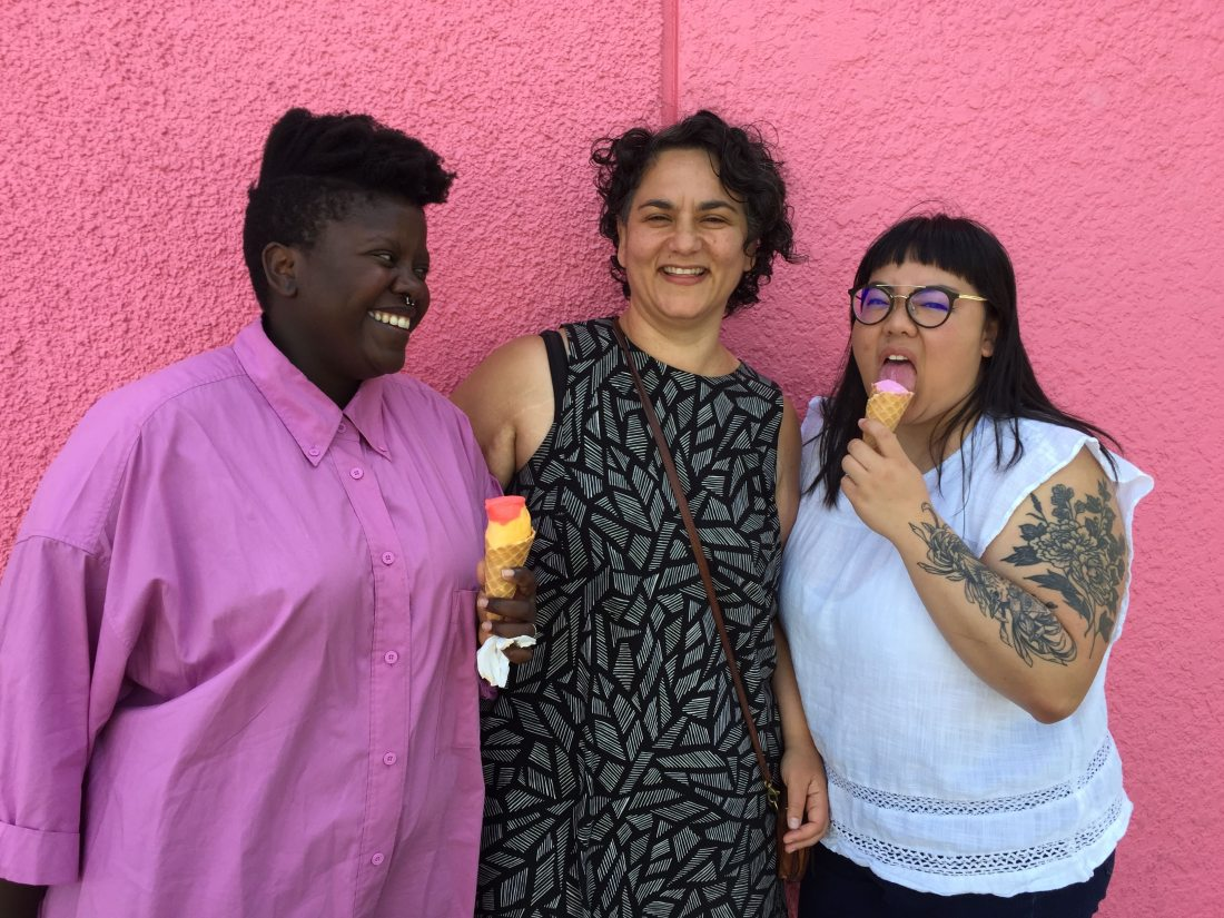 Well Rounded director Shana Myara with cast members Lydia and Joanne in front of a bright pink wall, eating ice cream