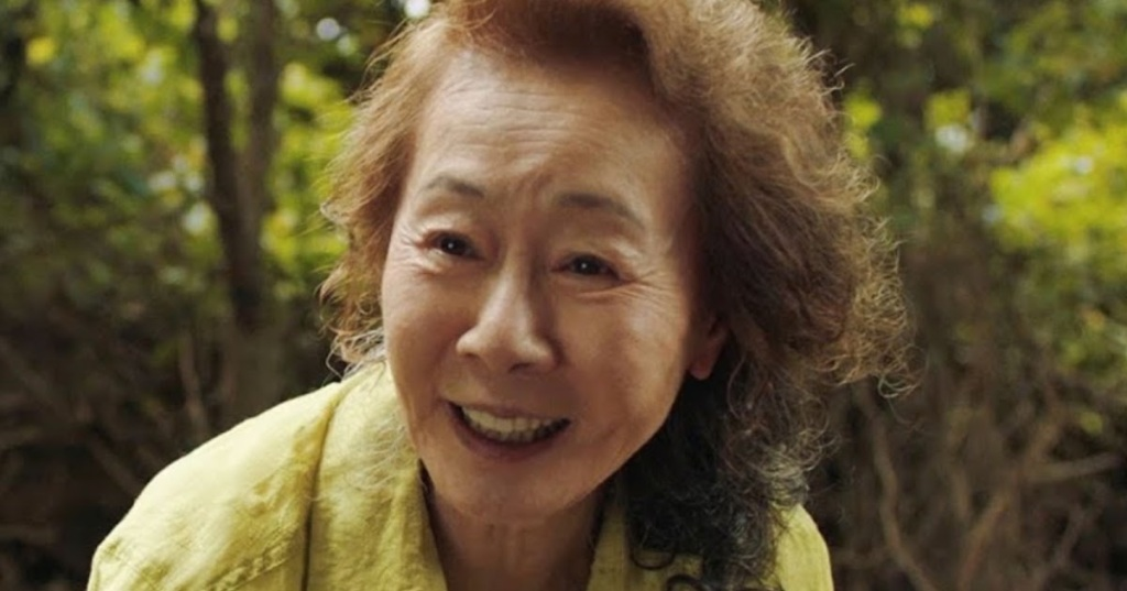 Image is from the film 'Minari'. An elderly woman in a forest leans down and smiles. She is wearing a yellow shirt.