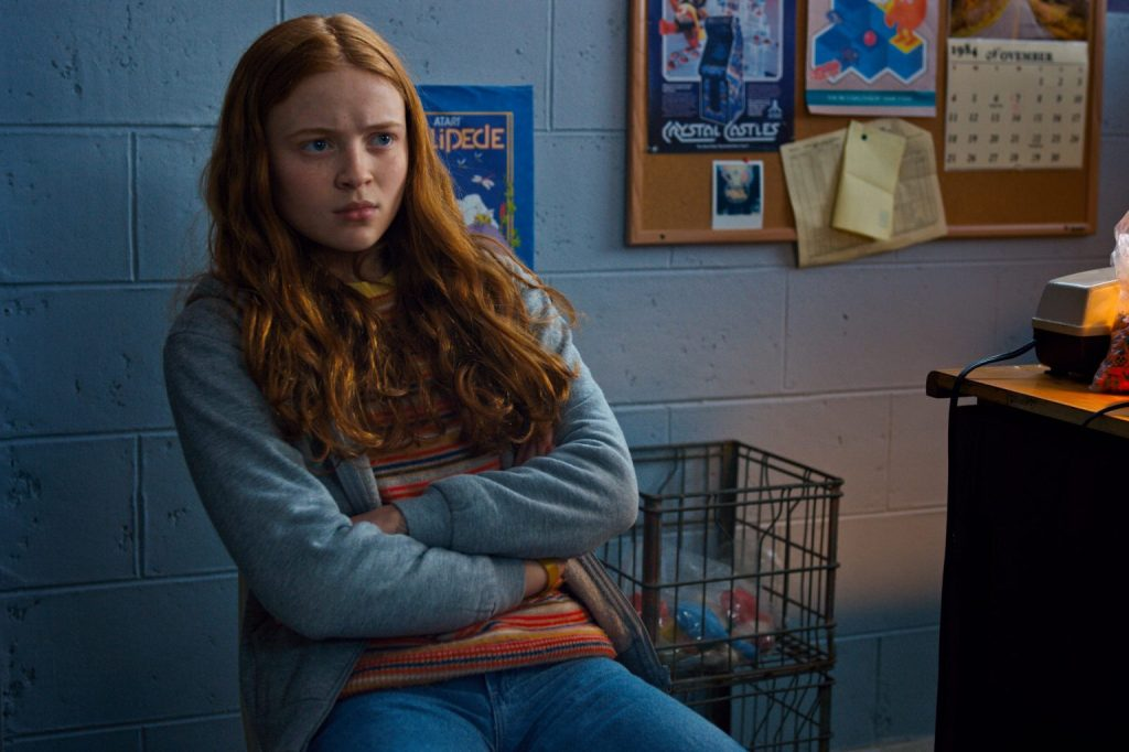 Max sits in a chair with her arms folded. She is wearing a light blue hoodie, which matches the colour of the brick wall behind her.