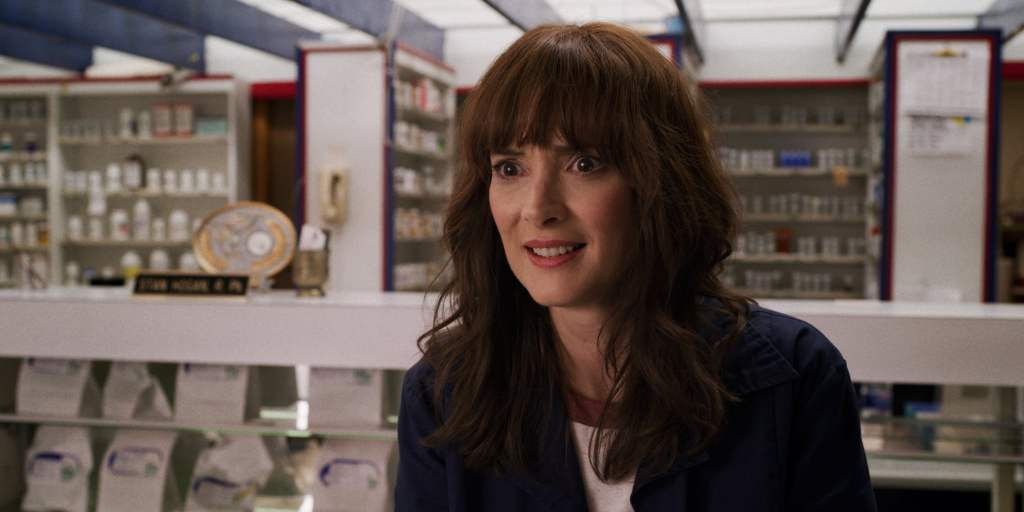 Joyce wears a concerned smiles in the middle of a pharmacy. She is wearing a blue coat and a white top.