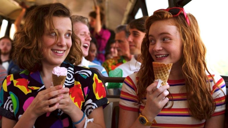Image is from the TV Series 'Stranger Things'. Two girls sit beside one another on a bus full of people. Both are wearing brightly coloured, patterned tops and are holding ice cream.