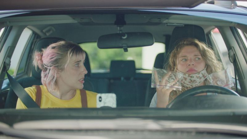 Image is from the film 'Recovery' (2021). Two women are sat in a car. One is wearing a bright yellow top and has faded pink hair, and she is talking to her friend who is holding ziploc bags over her hands and a floral mask around her chin.