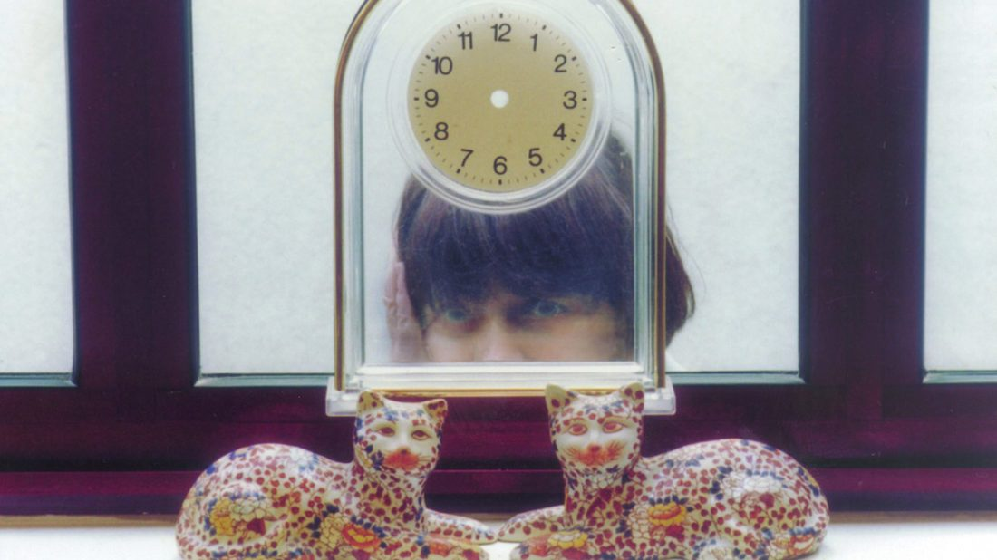 Image is from the film 'The Gleaners and I' (2000). The image shows an ornamental clock with no hands. In front of the clock sit a pair of ceramic cats, and behind the clock is the reflection of the film's director - Agnès Varda.