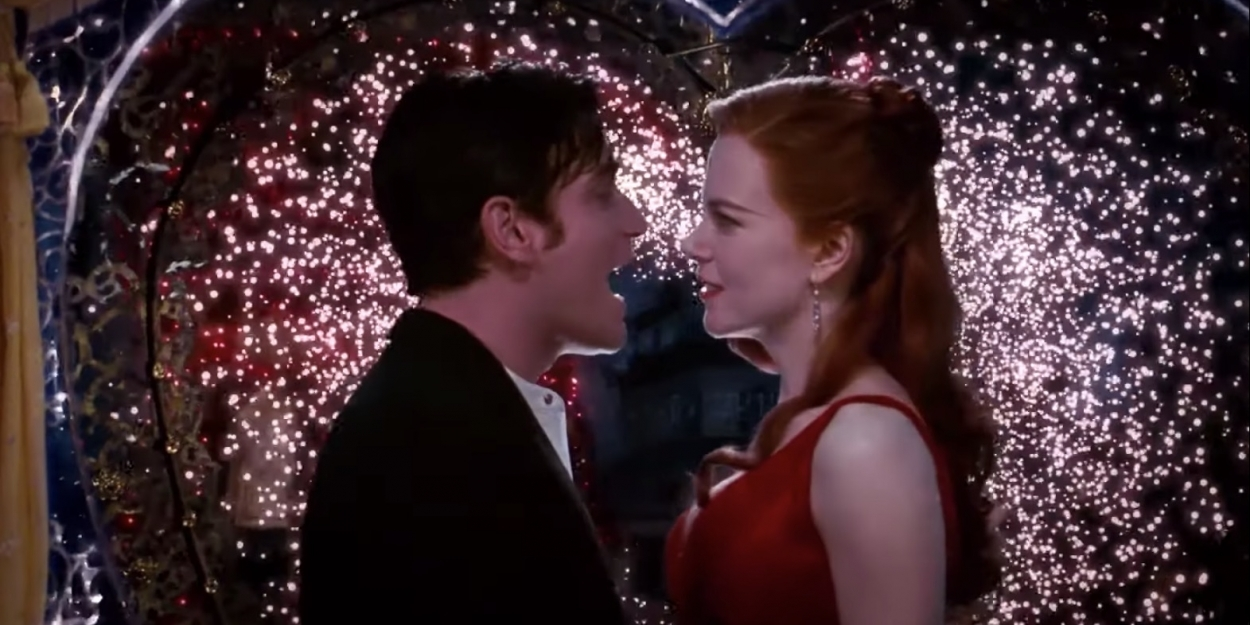 Image is from the film 'Moulin Rouge' (2001). In front of an array of sparks, a woman in a red dress and a man in a suit sing to one another as the look at one another lovingly.