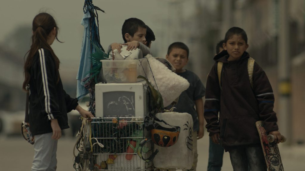 Five children standing in the streets of a Mexican city. They are pushing a basket full of found items- the only things they own.