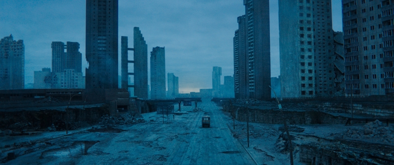 Image still from the sci-fi film Undergods. A wide-shot of a ruined, cold and blue-tinged apocalyptic landscape, full of burnt, crumbling buildings stretching into the sky. A lone vehicle drives through the middle of a long and empty road.