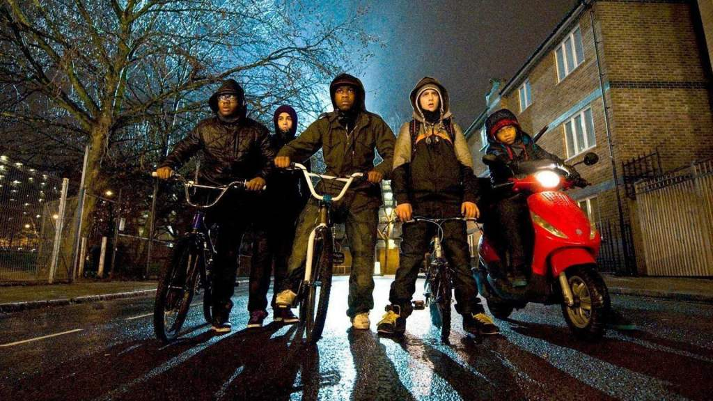 Image is from 'Attack on the Block' (2011). A group of teenagers on various bikes stand in the middle of a dark road and look shocked at something in front of them. Behind them, a blue light glows.