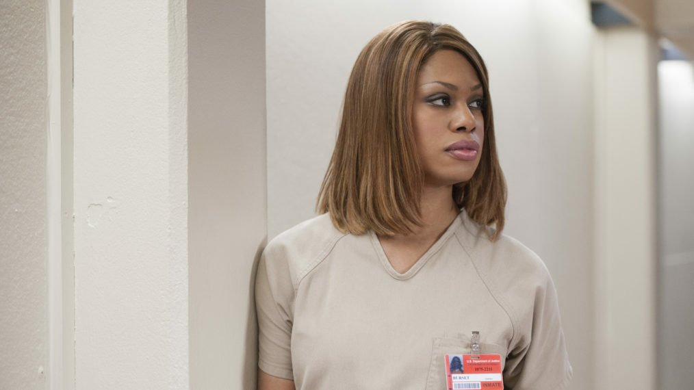 Orange Is The New Black's Sophia stands against the wall in prison uniform, hair bobbed and straightened and eyes looking away from the camera