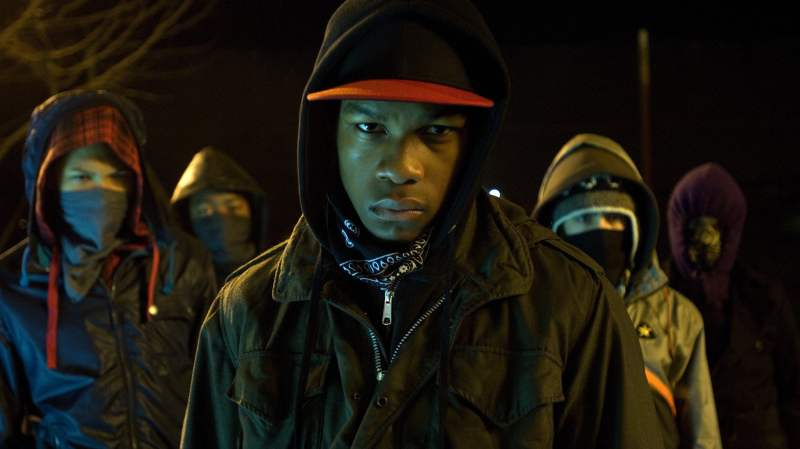 Image is from 'Attack on the Block' (2011). Image is from a group of teenagers which are coverings their faces with scarves and hoods. At the front is Moses, a young black teen who scowls. His face is uncovered.