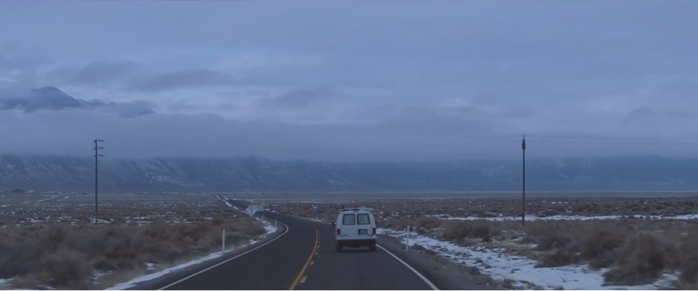Amidst a gloomy mountainous landscape, a white van drives down an open road. The landscape around it is scattered with snow.