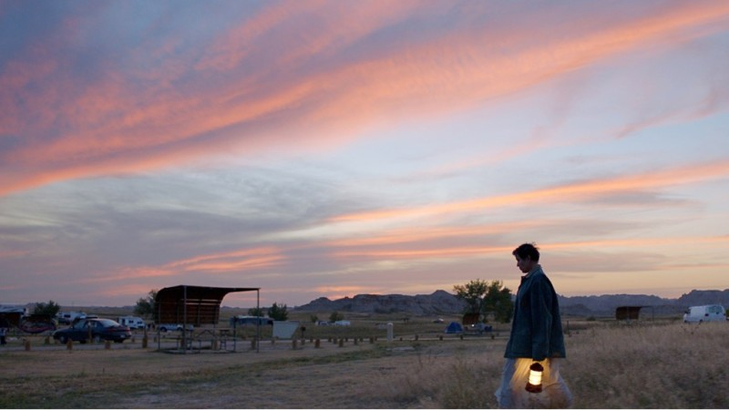Image is from the film 'Nomadland' (2020). A woman walks across a flat, arid landscape holding a lit lantern. She is silhouetted by mountains in the background and the sunset above her.