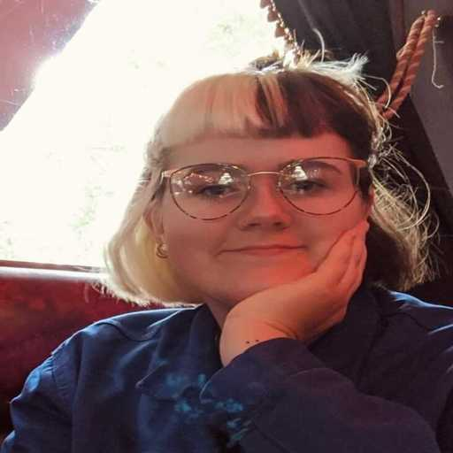 A selfie of Alex Greer, who has glasses. Her hair is short, half blonde and half dark brown. She is resting a hand on the side of her face.