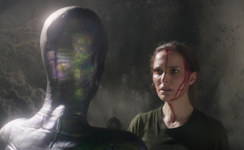 A woman wearing a dark green t-shirt with streaks of blood down her face and neck. She stares at a mysterious humanoid creature who has bright colours on the side of its head.