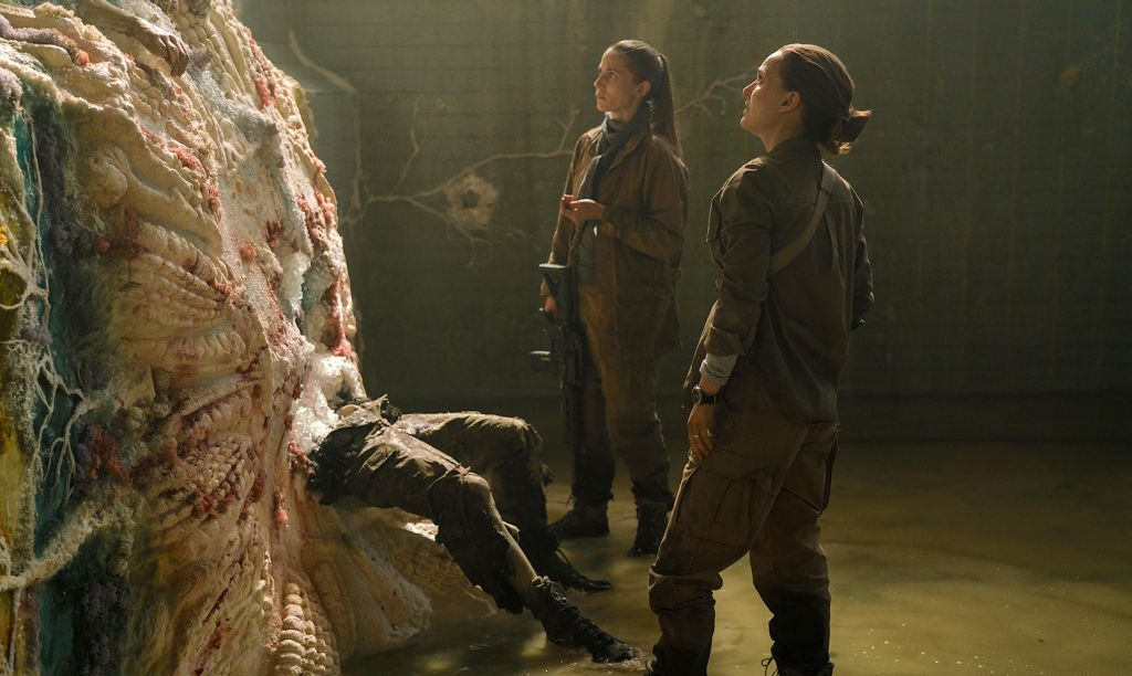 Two women dressed in dark green outfits look upon an alien life form. A pair of legs wearing matching pants that are ripped stick out from the bottom.