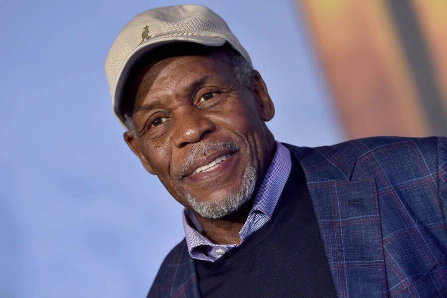 Danny Glover, a Black man in his 70s, smiles for the camera. He wears a navy plaid jacket, collared shirt, and tan baseball cap with a kangaroo.