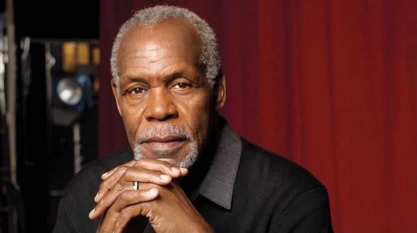 Danny Glover, a Black man in his 70s, poses in front of a red curtain. His hands are folded together.