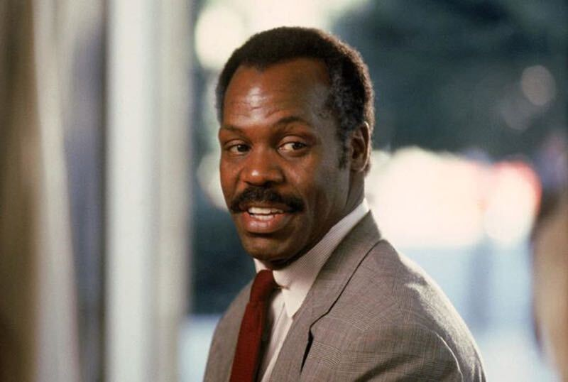 A Black man with short hair and a mustache. He wears a grey suit and red tie.